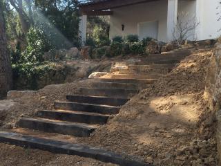 Escalier naturel traverses de chemin de fer en bois dans un jardin en pente